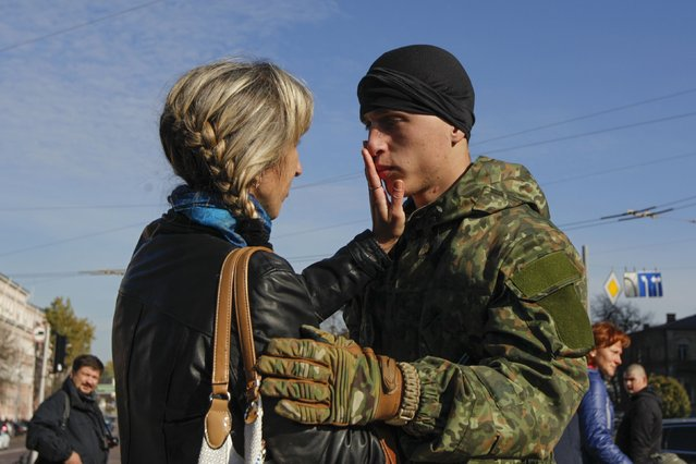 "A new volunteer of the Ukrainian interior ministry's ""Azov"" battalion says goodbye to his mother after taking his oath of allegiance to his country, in Kiev October 19, 2014. According to the battalion's commander, the volunteers will be headed to the frontlines in Eastern Ukraine, shortly after their ceremony. (Photo by Valentyn Ogirenko/Reuters)"