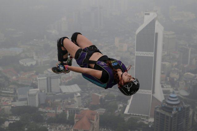 A BASE jumper is pictured against the skyline shrouded in a thick haze during the Kuala Lumpur Tower International Jump in Kuala Lumpur, Malaysia, 02 October 2015. More than 100 BASE jumpers take part in this extreme sport event, which enters its 15th year. The haze hovering over Malaysia is caused by the ongoing plantation and forest fires in the nearby Indonesian provinces of Sumatra and Kalimantan. (Photo by Fazry Ismail/EPA)