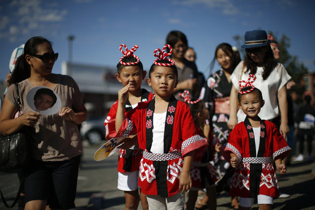 Sena Nagata, 7, Lana Osumi, 8, and Seri Nagata, 4, (L-R) wave as they watch a parade in the Little Tokyo area of Los Angeles, California August 10, 2014. (Photo by Lucy Nicholson/Reuters)