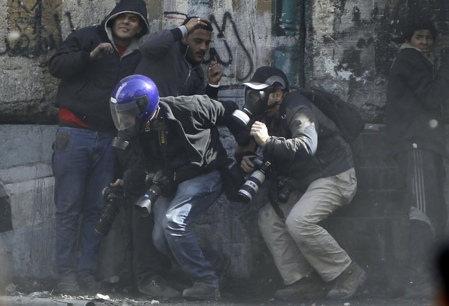 Photographers cower as protesters throw stones towards riot police along Sheikh Rihan street near Tahrir Square, on January 25, 2013. (Photo by Amr Abdallah Dalsh/Reuters/The Atlantic)