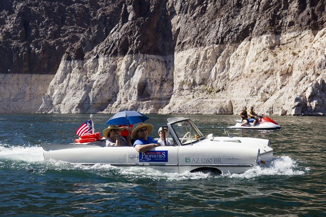 The Baker family of Lake Havasu, Arizona, head back to the marina in their 1965 Amphicar during the first Las Vegas Amphicar Swim-in at Lake Mead near Las Vegas, Nevada October 9, 2015. (Photo by Steve Marcus/Reuters)