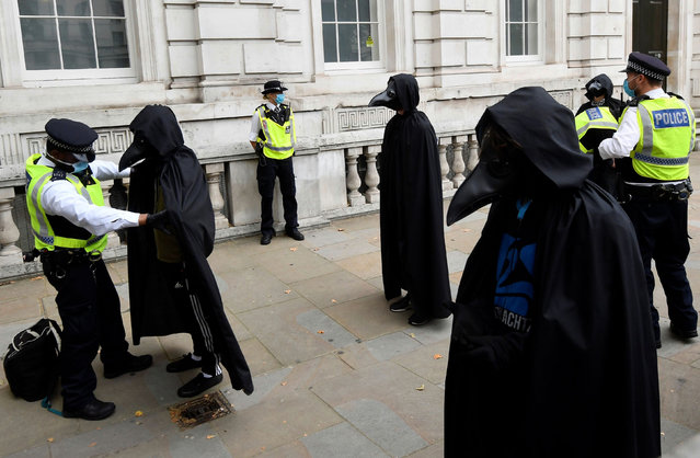 Police officers search members of the Animal Rebellion group dressed in a costume as they march during an Extinction Rebellion protest in London, Britain, September 8, 2020. (Photo by Toby Melville/Reuters)