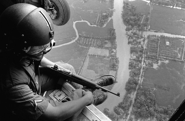 A Helmeted U.S. Helicopter Crewchief watches ground movements of Vietnamese troops from above during a strike against Viet Cong Guerrillas in the Mekong Delta Area, on January 2, 1963. The communist Viet Cong claimed victory in the continuing struggle in Vietnam after they shot down five U.S. helicopters. An American officer was killed and three other American servicemen were injured in the action. By 1963, nearly 16,000 American military personnel were deployed in South Vietnam. (Photo by AP Photo)