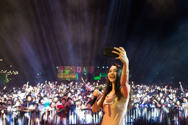 """This photo taken on January 28, 2018 shows Mary, a singer, taking selfie with the crowd as she performs at the """"&Proud"""" LGBT festival in Yangon. (Photo by Ye Aung Thu/AFP Photo)"""