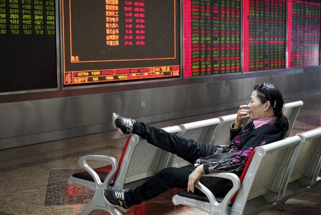 An investor rests on a chair in front of an electronic board showing stock information at a brokerage house in Beijing, China, October 13, 2015. China stocks were mixed on Tuesday after Beijing's September trade data left economists divided over whether the country's ailing trade sector is showing signs of turning around. (Photo by Reuters/Stringer)