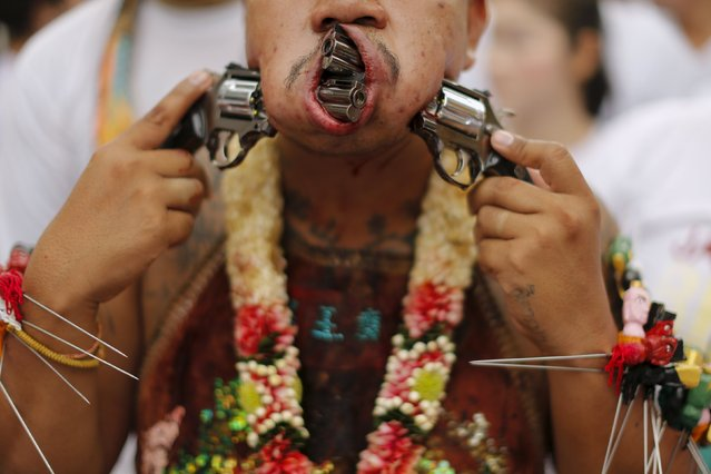 A devotee of the Chinese Bang Neow shrine walks with guns pierced through his cheeks during a procession celebrating the annual vegetarian festival in Phuket, Thailand October 18, 2015. (Photo by Jorge Silva/Reuters)