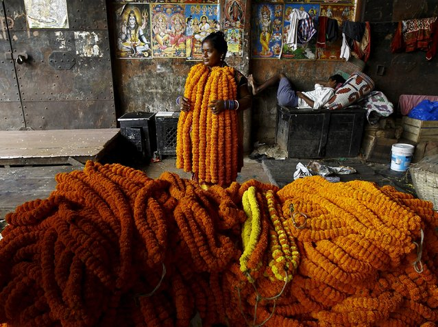 A woman selling garlands of marigold flowers waits for customers at a wholesale flower market during Durga Puja festival in Kolkata October 20, 2015. (Photo by Rupak De Chowdhuri/Reuters)