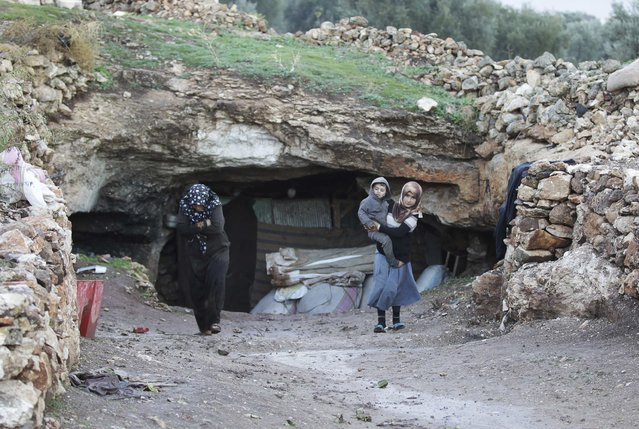 Displaced civilians walk out of an underground cave in Jabal al-Zawiya in the southern countryside of Idlib November 26, 2014. (Photo by Khalil Ashawi/Reuters)