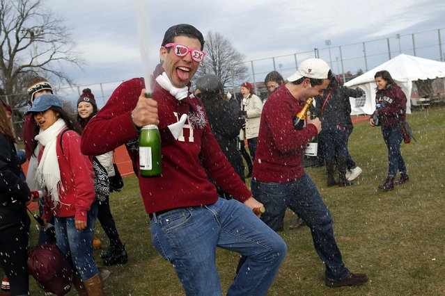 """Harvard University football fans spray champagne during a pre-game tailgate-style party outside the stadium before their football game against Yale University at Harvard in Cambridge, Massachusetts November 22, 2014. Known as """"The Game"""", the first Harvard versus Yale football game was played in 1875, making it one of the oldest rivalries in college sports. (Photo by Brian Snyder/Reuters)"""
