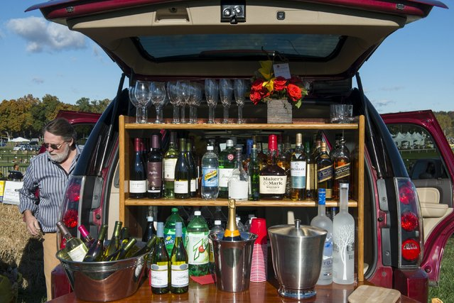 A man prepares the back of his car with bottles of alcohol for a tailgating party at the Far Hills Race Day at Moorland Farms in Far Hills, New Jersey, October 17, 2015. (Photo by Stephanie Keith/Reuters)