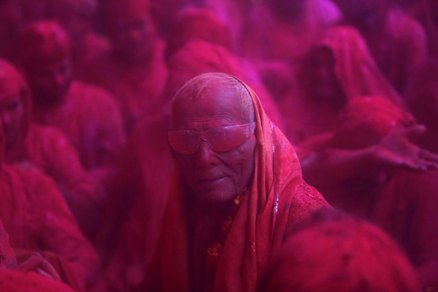"""A Hindu devotee looks on in a cloud of coloured powder inside a temple during """"Lathmar Holi"""" at the village of Barsana in the northern Indian state of Uttar Pradesh March 21, 2013. In a Holi tradition unique to Barsana and Nandgaon villages, men sing provocative songs to gain the attention of women, who then """"beat"""" them with bamboo sticks called """"lathis"""". Holi, also known as the Festival of Colours, heralds the beginning of spring and is celebrated all over India. (Photo by Vivek Prakash/Reuters)"""