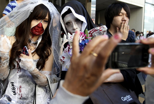 A visitor takes pictures of participants in costume during a Halloween parade in Kawasaki, south of Tokyo, October 25, 2015. (Photo by Yuya Shino/Reuters)