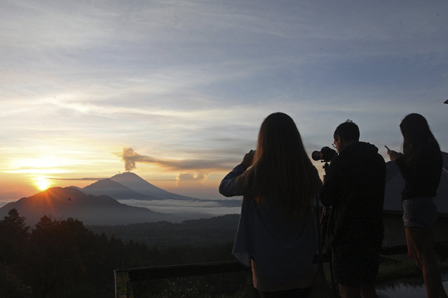 Tourists take photos of the Mount Agung volcano during a sunrise in Kintamani, Bali, Indonesia, Wednesday, December 13, 2017. Indonesia's disaster mitigation agency said the volcano remains at its highest alert level but most of Bali is safe for tourists. (Photo by Firdia Lisnawati/AP Photo)
