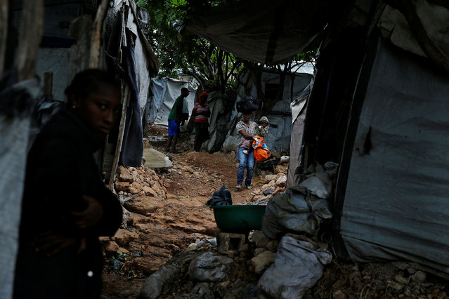 A woman carries her baby at a camp for displaced people while Hurricane Matthew approaches in Port-au-Prince, Haiti October 3, 2016. (Photo by Carlos Garcia Rawlins/Reuters)