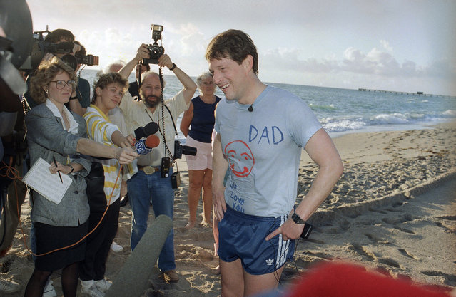 Sen. Albert Gore stands with hands on hips talking with reporters after a jog in Ft. Lauderdale beach, Wednesday, February 3, 1988. Sen. Gore wears a T-shirt given to him as a birthday present from his 4 children. (Photo by Marc Pesetsky/AP Photo)