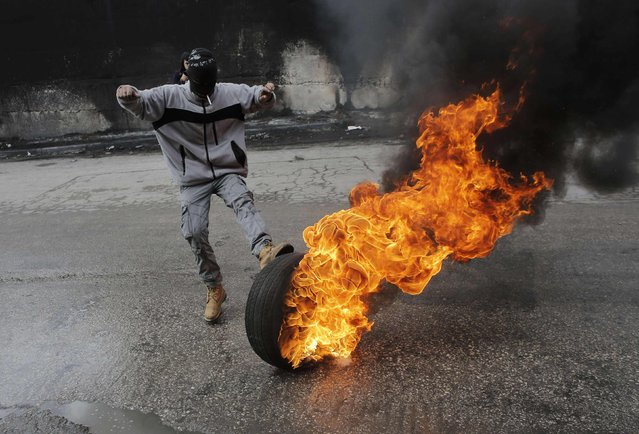 A Palestinian protester kicks a burning tyre during clashes with Israeli troops near Israel's controversial barrier that separates the West Bank town of Abu Dis from Jerusalem November 17, 2014. A Palestinian bus driver was found hanged inside his vehicle on Monday, an incident Israeli police described as a suicide but which the driver's family said they believed was an attack. (Photo by Ammar Awad/Reuters)