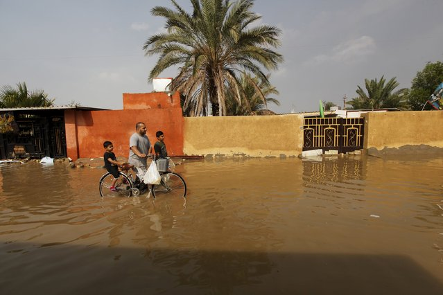 People cross a flooded street after heavy rainfall in Baghdad, Iraq, October 31 2015. (Photo by Ahmed Saad/Reuters)