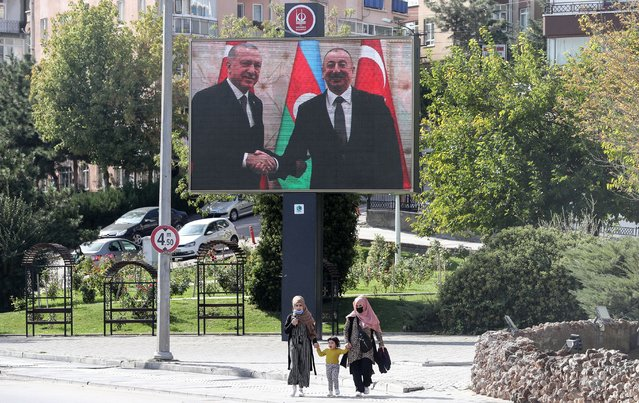 Two women walk past a large image of Turkish President Recep Tayyip Erdogan (L) and Azerbaijani President Ilham Aliyev shaking hands displayed on a huge screen in the Kecioren district of Ankara on October 21, 2020. The origins of a flareup in fighting over Nagorno-Karabakh that has now killed hundreds and threatens to involve regional powers Turkey and Russia are hotly contested and difficult to independently verify. Both sides accuse the other of striking first on September 27 over the ethnic Armenian region of Azerbaijan. (Photo by Adem Altan/AFP Photo)