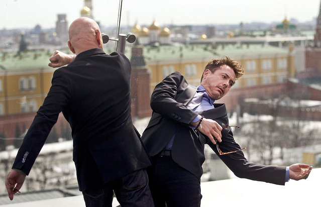 Ben Kingsley pretends to strike Robert Downey Jr., during a photo opportunity to promote their new movie Iron Man 3, on the roof of a hotel in Moscow, on April 10, 2013. (Photo by Ivan Sekretarev/Associated Press)