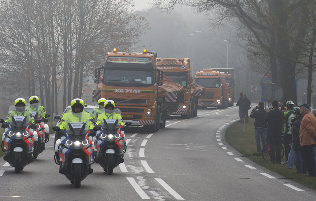 People line the road as trucks carrying parts of the wreckage of downed Malaysia Airlines flight MH17 arrive from the Ukraine at Gilze-Rijen military base, Netherlands, Tuesday, December 9, 2014. The Boeing 777 plummeted from high altitude over eastern Ukraine on July 17 2014, killing all 298 passengers and crew on board. Two-thirds of the victims hailed from the Netherlands, from where the Dutch government is now leading the investigation. (Photo by Peter Dejong/AP Photo)