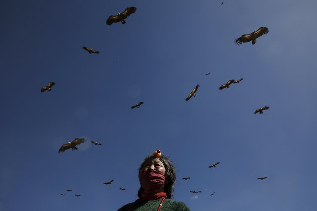Vultures fly over an ethnic Tibetan woman from Kham area wearing traditional amber headwear during a sky burial near the Larung valley located some 3700 to 4000 metres above the sea level in Sertar county, Garze Tibetan Autonomous Prefecture, Sichuan province, China November 1, 2015. (Photo by Damir Sagolj/Reuters)