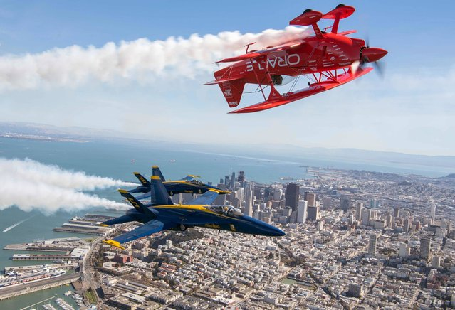 The US Navy Blue Angels numbers 5 and 6 fly below Sean Tucker (above) as he pilots the Oracle Challenger III over San Francisco, California as part of a practice run for Fleet Week on October 6, 2016. (Photo by Josh Edelson/AFP Photo)