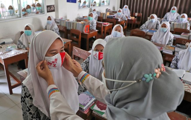 A public health official shows how to properly wear face masks to students during a class teaching health protocols for curbing the spread of coronavirus outbreak at the Daarul Rahman Islamic Boarding School in Jakarta, Indonesia, Wednesday, November 18, 2020. (Photo by Tatan Syuflana/AP Photo)
