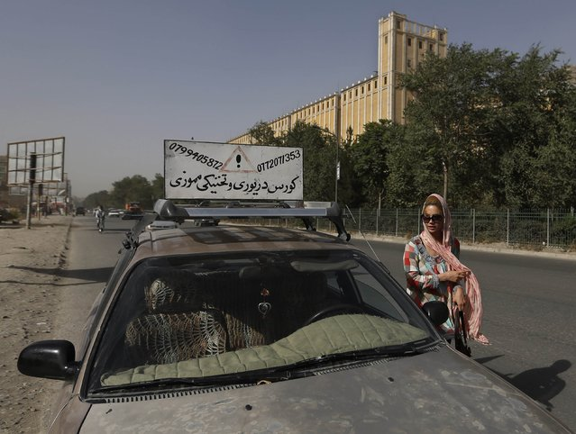 Kanaz, 21, gets out of a car after a practical driving lesson in Kabul August 14, 2014. (Photo by Mohammad Ismail/Reuters)