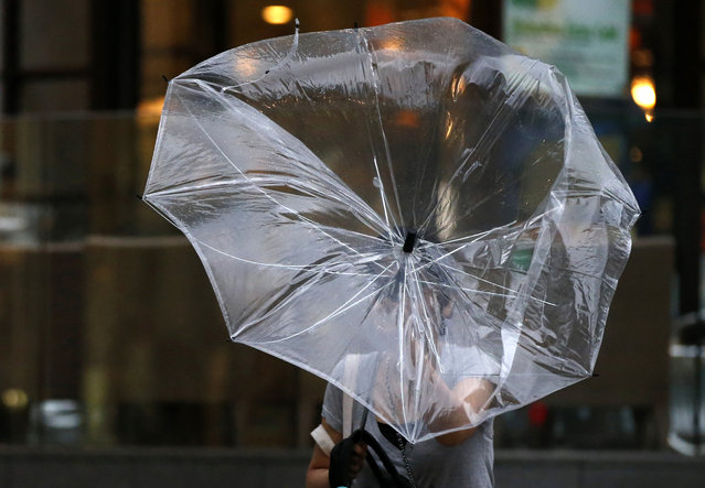 A woman struggles with an umbrella in strong winds and rain caused by Typhoon Halong in Tokyo August 10, 2014. (Photo by Toru Hanai/Reuters)