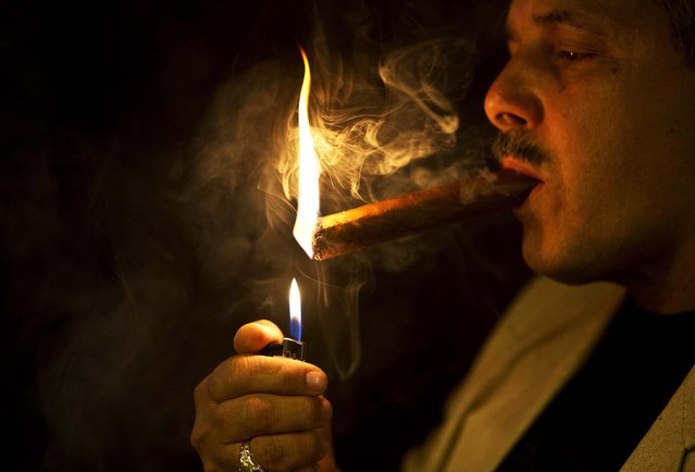 A man lights a cigar in a cigar club shop in Havana, Cuba, Friday, December 19, 2014. The coveted Cuban cigar is set to make its first legal appearance in the U.S. in years, with relaxed guidelines allowing American travelers to return with a few of the once-forbidden items in their suitcases. (Photo by Ramon Espinosa/AP Photo)