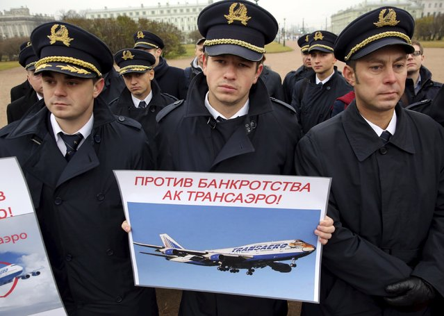 """Pilots and flight attendants picket in support of troubled airline Transaero in the Field of Mars in St. Petersburg, Russia November 8, 2015. Transaero, Russia's second-biggest airline, is laden with debt. Two of its main creditors, Sberbank and Alfa Bank, have filed bankruptcy cases against the airline after it lost out on a lifeline deal with competitor Aeroflot. The placard read, """"Against of Transaero airline bankruptcy"""". (Photo by Peter Kovalev/Reuters)"""