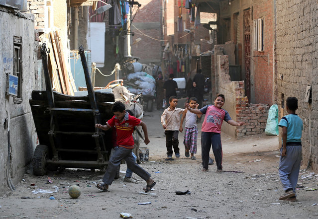 Children play with a ball in front of their homes in Ezbet Khairallah in Cairo, Egypt October 4, 2016. (Photo by Mohamed Abd El Ghany/Reuters)