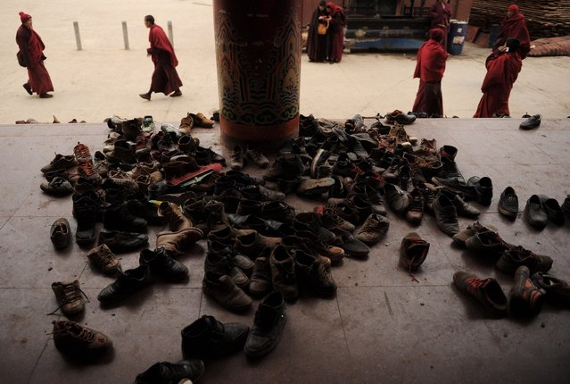 This photo taken on April 4, 2013 shows apprentice Buddhist monks leaving their shoes outside before a debating session in Seda Monastery, the largest Tibetan Buddhist school in the world, with up to 40,000 monks and nuns in residence for some parts of the year. Seda, known to Tibetans as Serthar is located in Ganzi prefecture in the west of China's Sichuan province and has become a hotbed of protests and violence since the Tibetan uprisings of March 2008. (Photo by Peter Parks/AFP Photo)