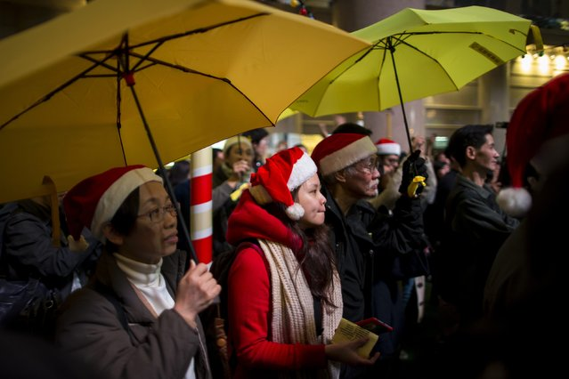 Pro-democracy protesters, holding up yellow umbrellas, a symbol of the Occupy Central civil disobedience movement, attend a protest at Times Square in Hong Kong early December 25, 2014. Hundreds of people gathered before midnight on Christmas eve calling for universal suffrage and for Beijing to withdraw its decision on political reform. (Photo by Tyrone Siu/Reuters)