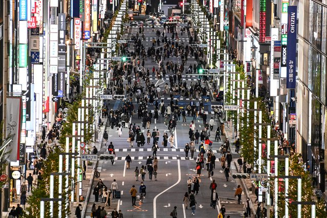 People walk on a street in Tokyo's Ginza area on November 23, 2020. (Photo by Charly Triballeau/AFP Photo)