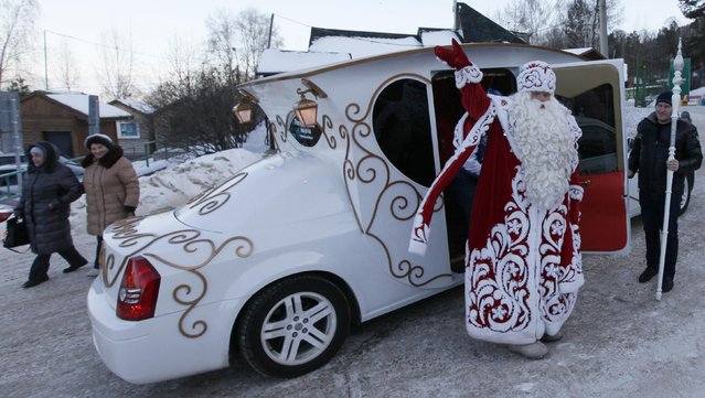A man dressed as Father Frost, Russian equivalent of Santa Claus, welcomes people as he leaves a car during a children's celebration at Father Frost's forest residence set up inside a local zoo in the Taiga district, outside Krasnoyarsk, Siberia, December 20, 2014. Russia's main Father Frost from Veliky Ustyug visited Krasnoyarsk on Saturday, according to local media and the event organizers. (Photo by Ilya Naymushin/Reuters)