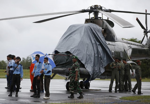 An Indonesian military helicopter, used in recovery efforts for the missing AirAsia plane, sits idle on the tarmac at Iskandar Airport during bad weather in Pangkalan Bun, Central Kalimantan, December 31, 2014. (Photo by Darren Whiteside/Reuters)