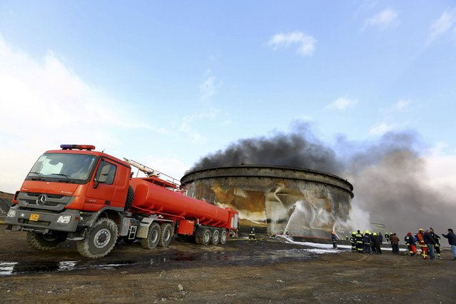 Fire-fighters work to put out a fire at a storage oil tank in the port of Es Sider January 2, 2015. (Photo by Reuters/Stringer)