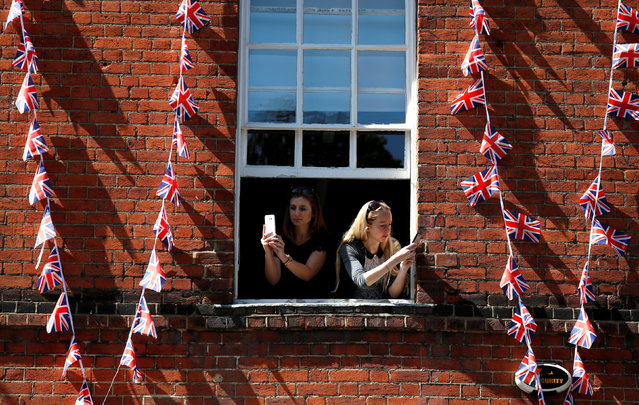 Women take photos on their smartphones as they lean out of the window of a building near Windsor Castle in Windsor, Britain, May 17, 2018. (Photo by Damir Sagolj/Reuters)