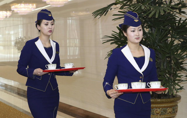 Female staff members carry tea cups at the Pyongyang Airport in Pyongyang, North Korea, Saturday, March 31, 2018. From aging crooners to bubbly K-Pop starlets, some of South Korea's biggest pop stars flew to North Korea on Saturday for rare performances that highlight the sudden thaw in inter-Korean ties after years of tensions over the North's nuclear ambitions. (Photo by Korea Pool via AP Photo)