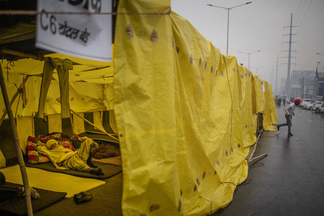 A farmer lies down inside a makeshift tent pitched on a major highway in a protest against new farm laws while it rains at the Delhi-Uttar Pradesh state border, India, Monday, January 4, 2021. (Photo by Altaf Qadri/AP Photo)