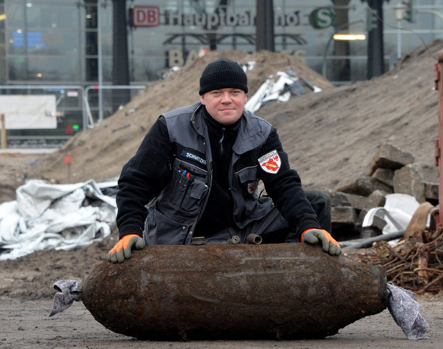 Ordnance disposal expert Mike Schwitzke of the bomb disposal unit of the police kneels behind a defused 250 kilogram World War II bomb in Potsdam, Germany, 07 January 2015. Around 10,000 residents had to be evacuated from their homes in the city centre of Potsdam during the disarming of the bomb, which was found during construction work near Potsdam's central train station (background). (Photo by Bernd Settnik/EPA)