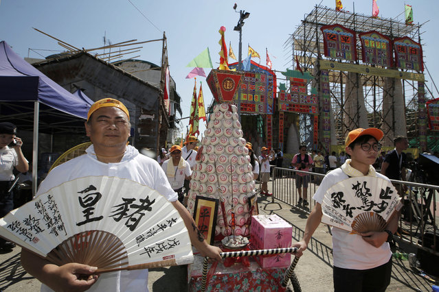 Villagers carry a bun tower during a parade on the outlying Cheung Chau island in Hong Kong to celebrate the Bun Festival Tuesday, May 22, 2018. (Photo by Kin Cheung/AP Photo)