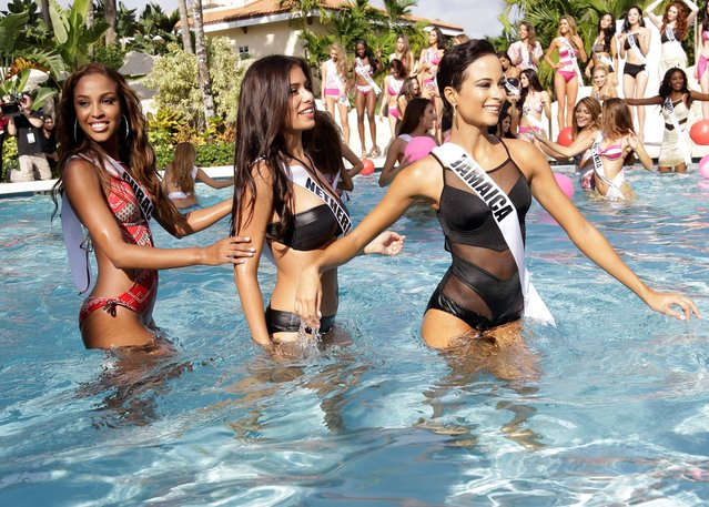Miss Universe contestants Laurien Angelista, of Curacao, left, Yasmin Verheijen, of the Netherlands, and Kaci Fennell, of Jamaica, walk in the pool during the Yamamay swimsuit runway show, Wednesday, January 14, 2015, in Doral, Fla. The Miss Universe pageant will be held January 25 in Miami. (Photo by Lynne Sladky/AP Photo)