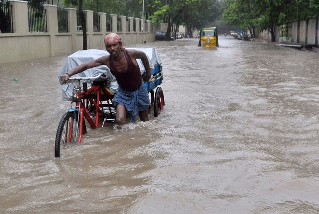 An Indian labourer pushes his cycle trishaw through floodwaters in Chennai on December 1, 2015, during a downpour of heavy rain in the southern Indian city. Heavy rains pounded several parts of the southern Indian state of Tamil Nadu and inundating most areas of Chennai, severely disrupting flights, train and bus services and forcing the postponment of half-yearly school exams. (Photo by AFP Photo/Stringer)
