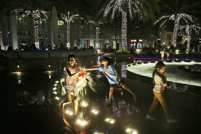In this April 9, 2015 photo, children enjoy playing in a fountain at the Marina waterfront in Dubai, United Arab Emirates. Dubai's rapid transformation from a desert outpost into one of the world's most architecturally stunning cities is mapped out in Marina. Where just 15 years ago there was empty, flat land, today a bustling neighborhood thrives centered around a canal and an impressive skyline. (Photo by Kamran Jebreili/AP Photo)