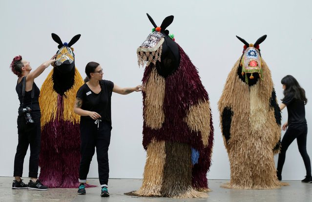 Dressers make last minute adjustments to the costumes of dancers performing as horses during a press preview of American artist Nick Cave's first major work shown in Australia, entitled HEARD.SYD in Sydney, November 8, 2016. (Photo by Jason Reed/Reuters)