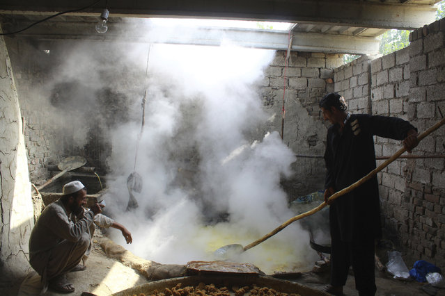 "Pakistani vendors make ""gur"", or jaggery, prepared from molasses of sugarcane in Peshawar, Pakistan, Wednesday, October 19, 2016. (Photo by Mohammad Sajjad/AP Photo)"