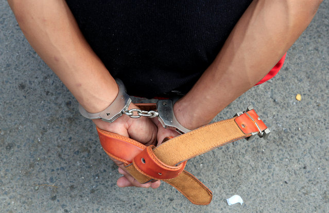 A man is handcuffed for questioning following an identity check during an anti-drugs operation by members of the Philippine National Police (PNP) in metro Manila, Philippines November 10, 2016. (Photo by Romeo Ranoco/Reuters)