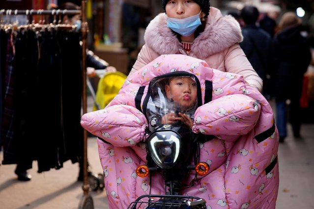 A woman wearing a face mask rides a bicycle with a child, following an outbreak of the coronavirus disease (COVID-19) in Wuhan, Hubei province, China on February 8, 2021. (Photo by Aly Song/Reuters)